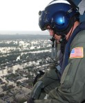 A Coast Guard helicopter crewman scours New Orleans neighborhoods looking for citizens in distress after Hurricane Katrina.  (USCG photo by PA1 Kyle Niemi)